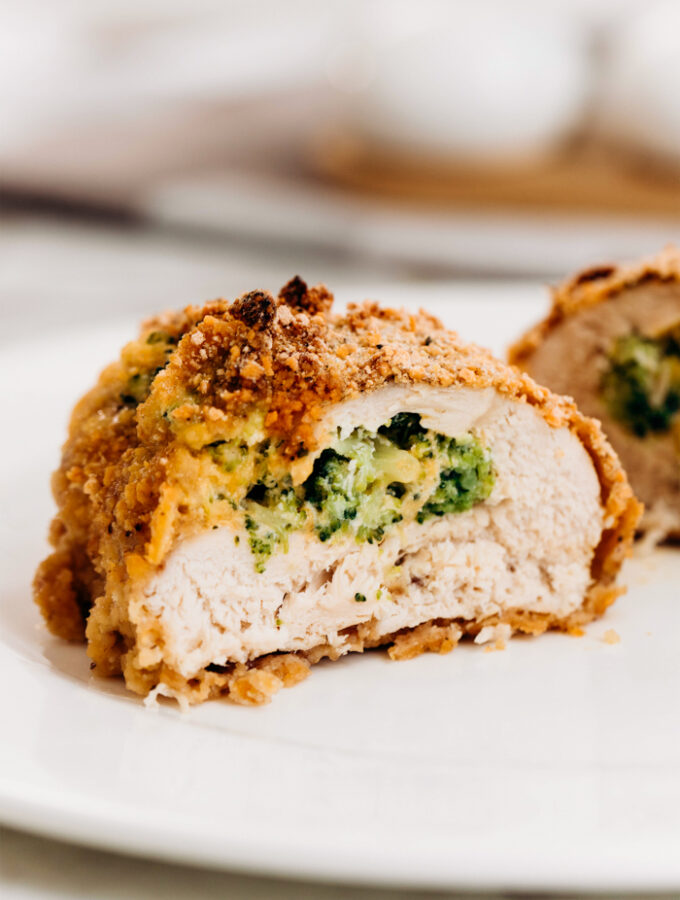 A piece of broccoli cheese stuffed chicken, cut in half, and exposing the cheese and broccoli stuffing