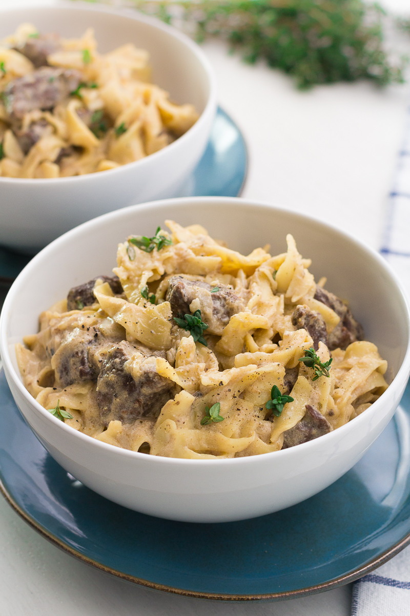 Slow cooker beef stroganoff in a white bowl