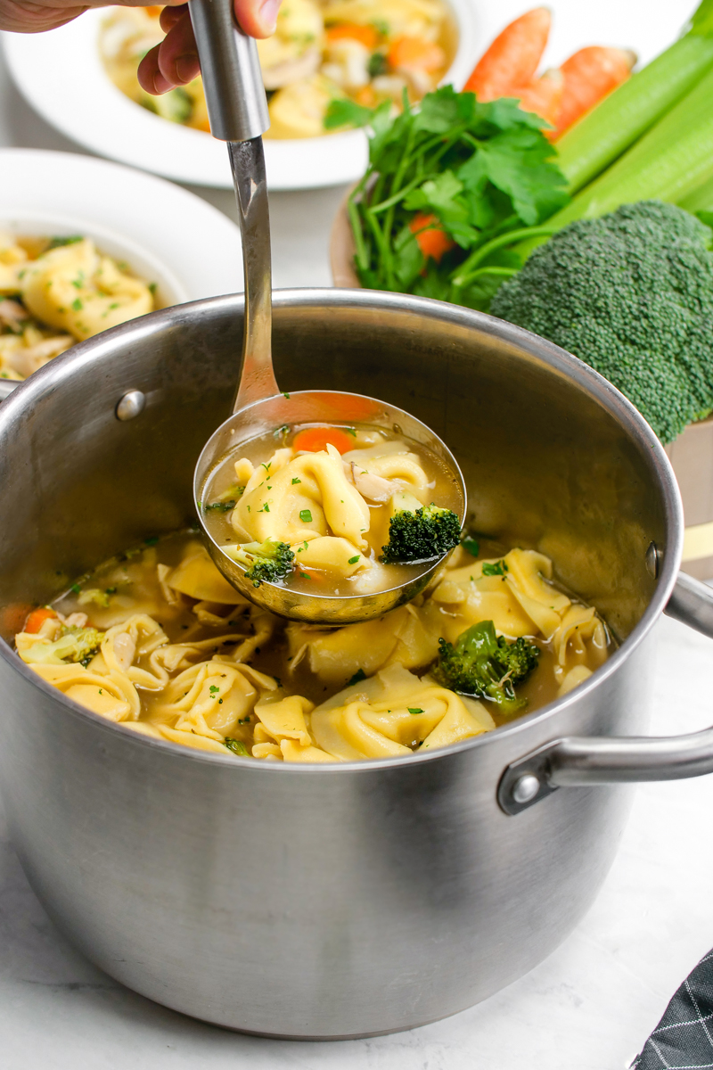 Chicken tortellini soup in a soup pot with a ladel
