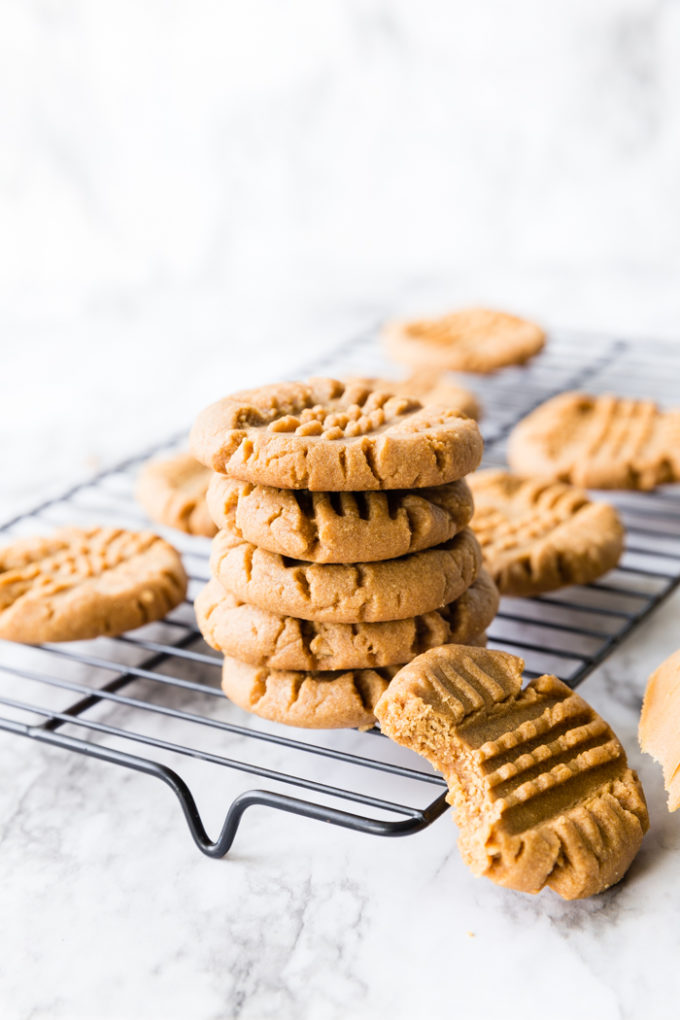 A cooling rack with a stack of delicious peanut butter cookies.