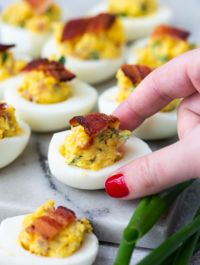 a hand grabbing a bacon cheddar ranch deviled egg off a tray of deviled eggs