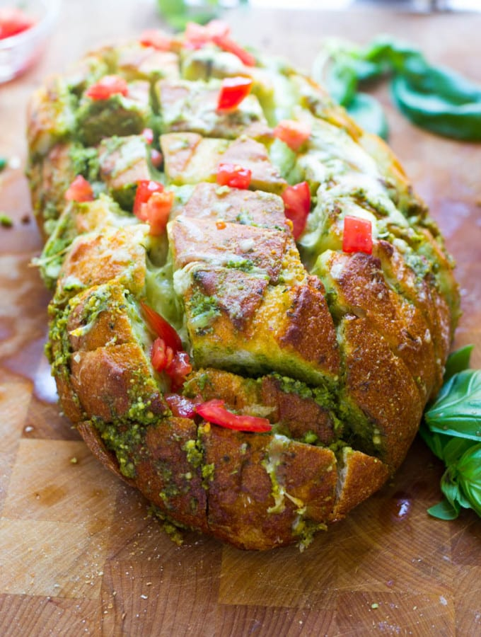 This scrumptious pull apart bread full of cheesy goodness and pesto is the ideal way to use up all that fresh basil hanging around in your garden now! Plus there has never been an easier way to make day old bread taste scrumptiously delicious!