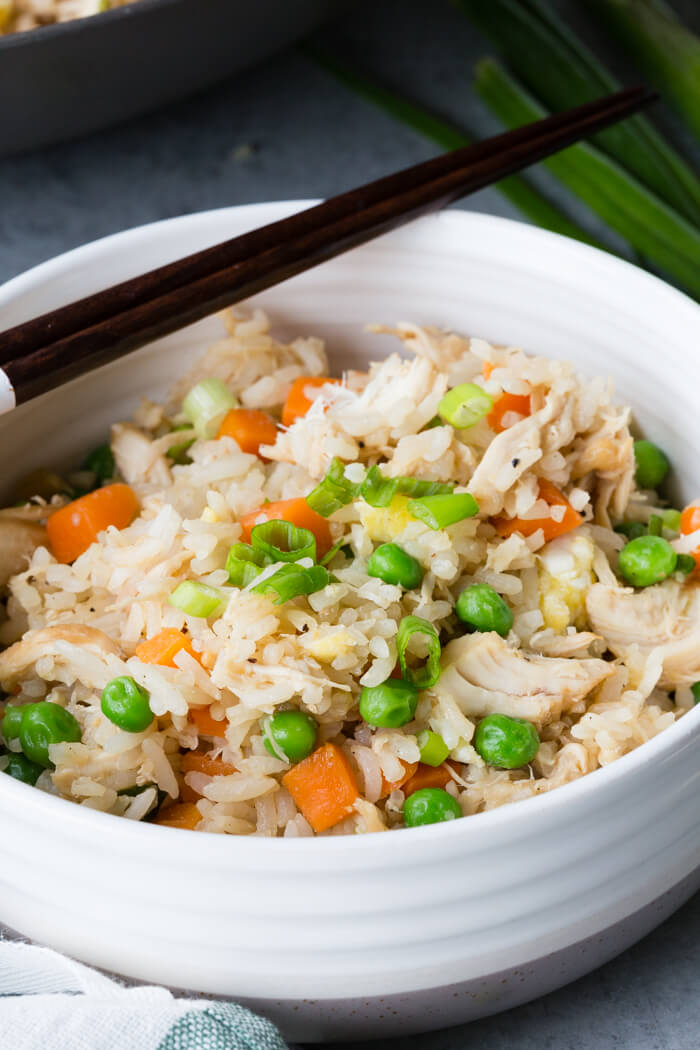 Chicken fried rice in a white bowl with a black chopstick