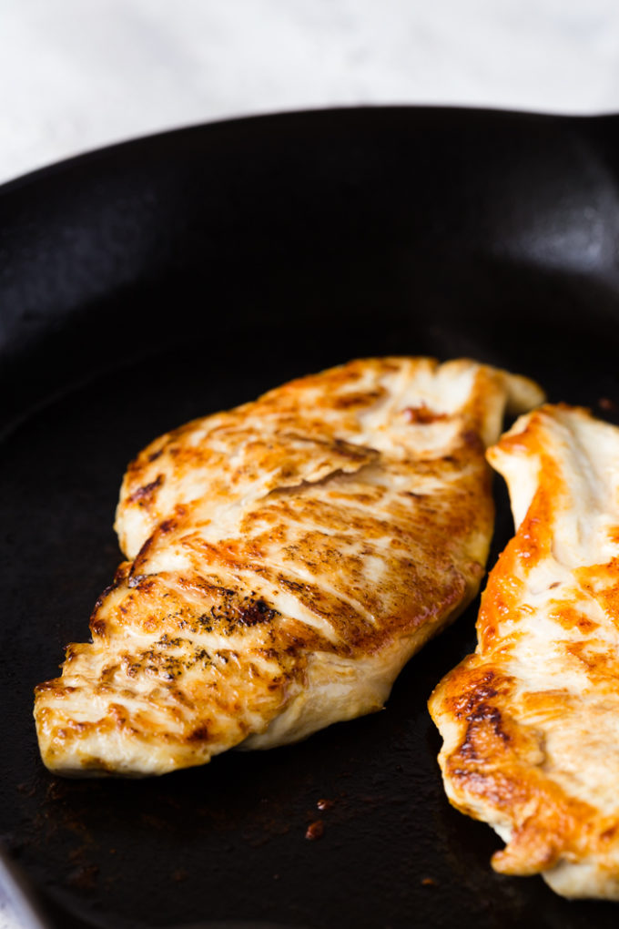 Searing the creamy tuscan skillet chicken on each side.