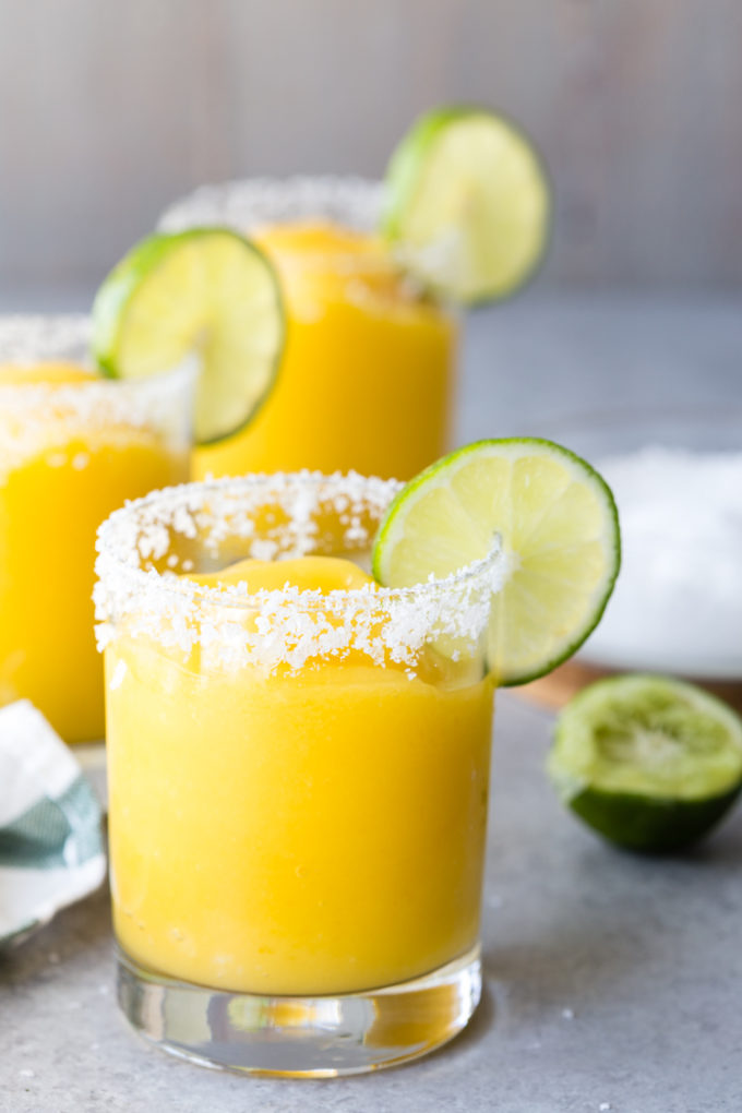 Frozen Mango Margaritas in a glass with a salted rim.