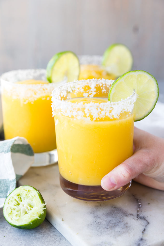 Mango Margaritas raise a glass, salted rim, with lime, frozen