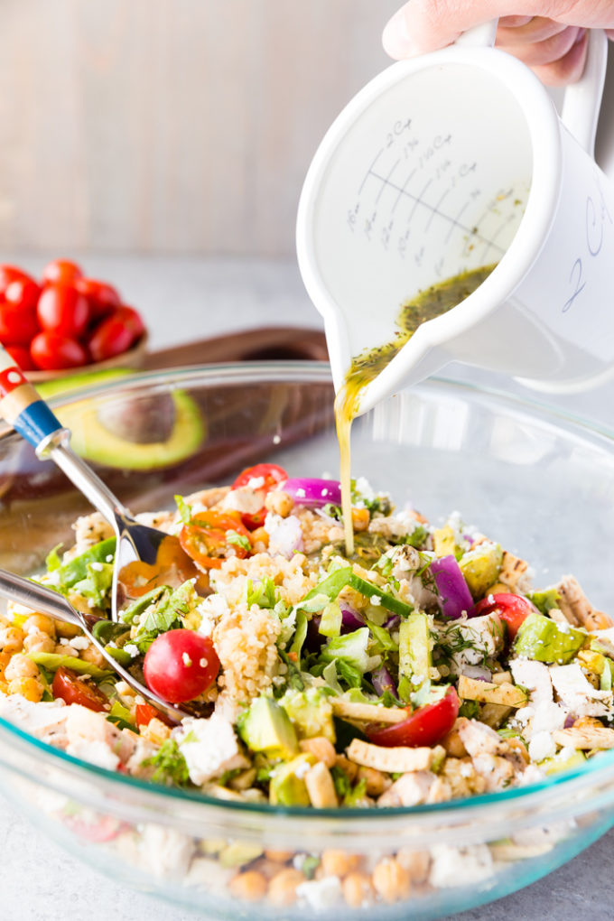 Greek Chicken Chopped Salad with a Greek dressing being poured over the top