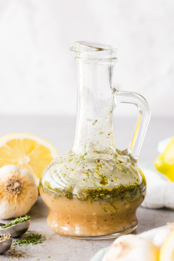 Bottle of Greek Chicken Marinade with lemons, garlic, and herbs around it.