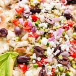 close up picture of greek chicken nachos with pita chips and toppings.