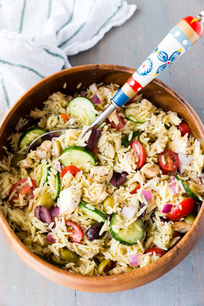 Brown bowl with greek chicken orzo pasta salad inside and spoon.