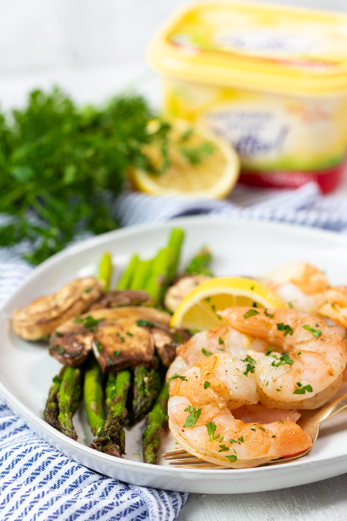 A white plate covered with honey lemon garlic shrimp and asparagus and mushrooms.