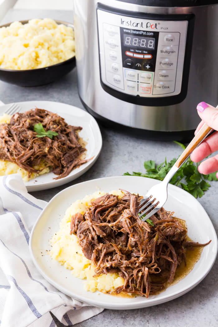 Pressure cooker pot roast on a bed of mashed potatoes in front of an instant pot