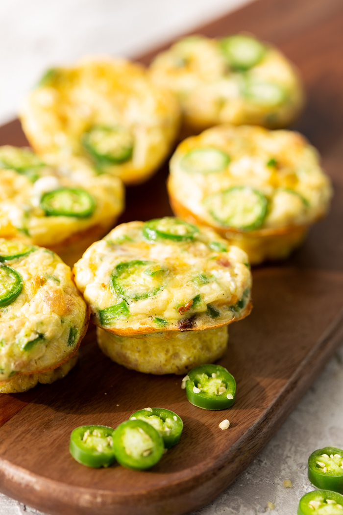 six jalapeno popper egg muffins on a cutting board with some sliced jalapenos
