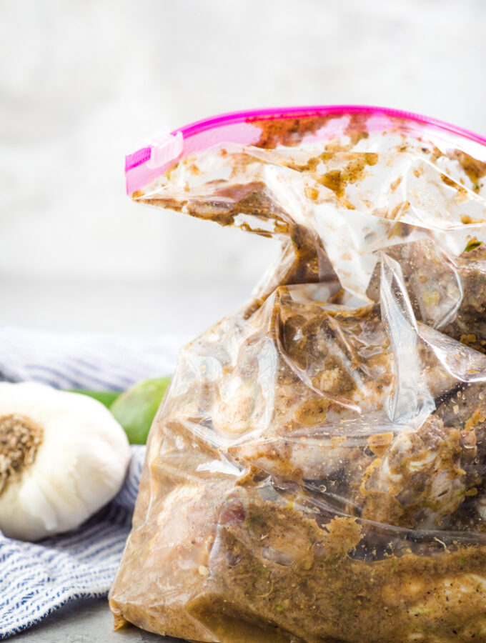 A zip top bag with chicken in it marinating in a jerk chicken marinade
