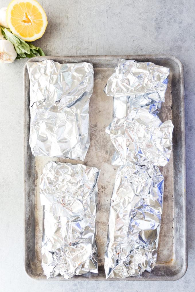Cooking lemon butter salmon foil packets, baking them delicious