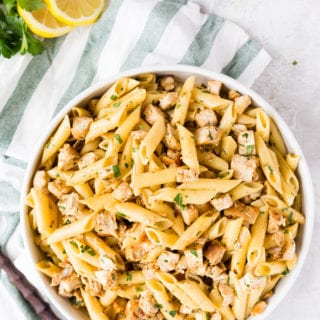 Easy to make Lemon Chicken Pasta, in a big white bowl, on a green napkin, with fresh lemons