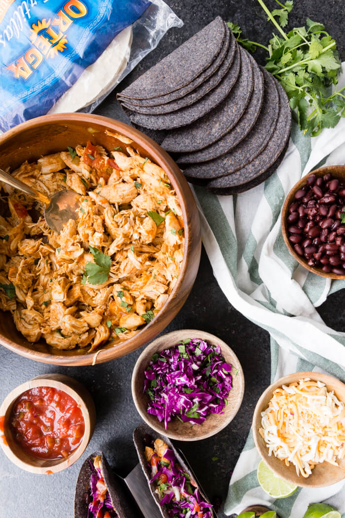 Instant Pot Shredded Chicken, Salsa, Cabbage, Cheese, and Black Beans in wooden bowl ready for a taco bar with blue corn taco shells