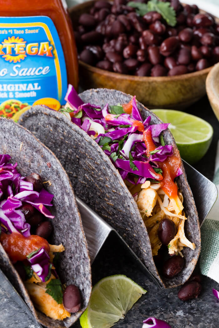 instant pot shredded chicken taco in a blue corn taco shell with black beans and taco sauce in the background