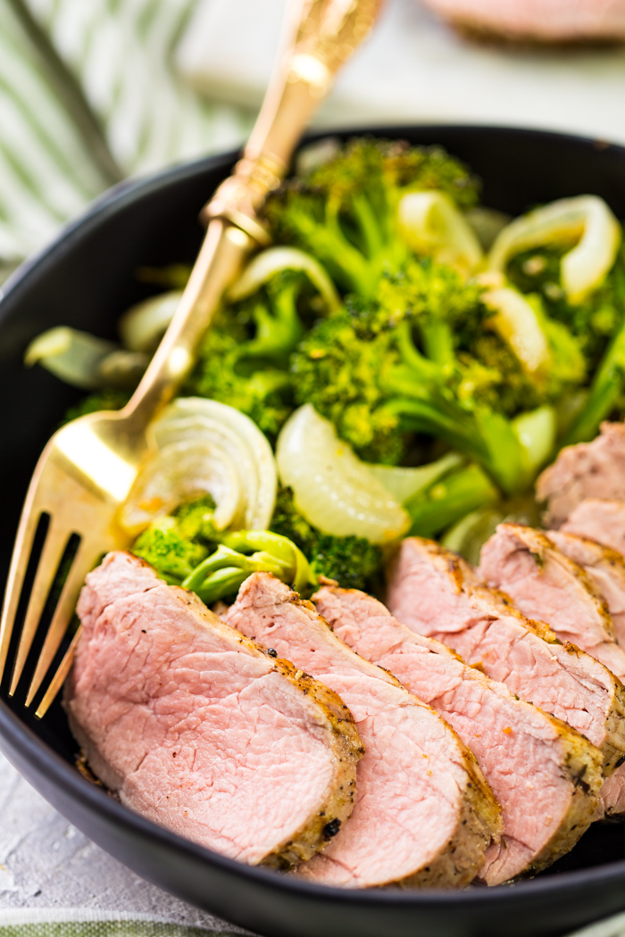 Pork tenderloin on a black bowl with vegetables and sliced pork tenderloin