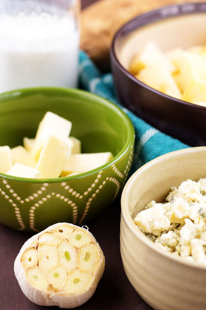 Garlic bulb, bowl of bleu cheese, bowl of butter, bowl of potatoes - ingredients for Roasted Garlic Bleu Cheese Mashed Potatoes.