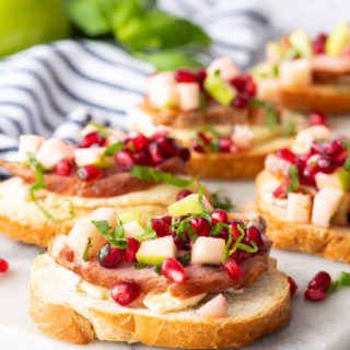 Roasted Pork Crostini with apple and pomegranate on a marble cutting board