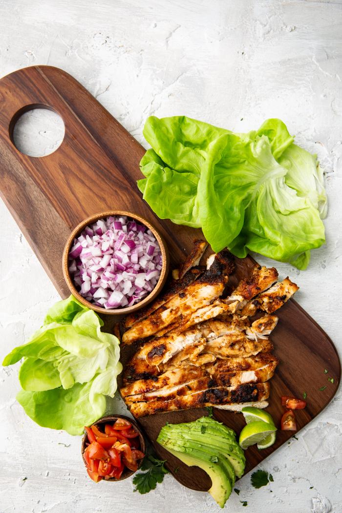 Chicken taco lettuce wrap ingredients on a cutting board.