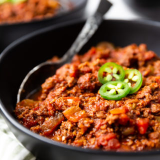 a black bowl full of keto chili, topped with jalapenos. This low carb chili has a spoon in it.