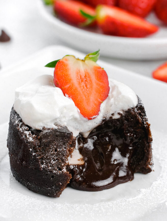 Chocolate molten lava cake, with the lava coming out the front, topped with whipped cream and strawberries