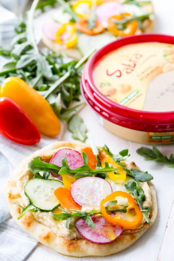 Vegetable Hummus Flatbread is flatbread slathered in hummus and topped with mandolin sliced veggies