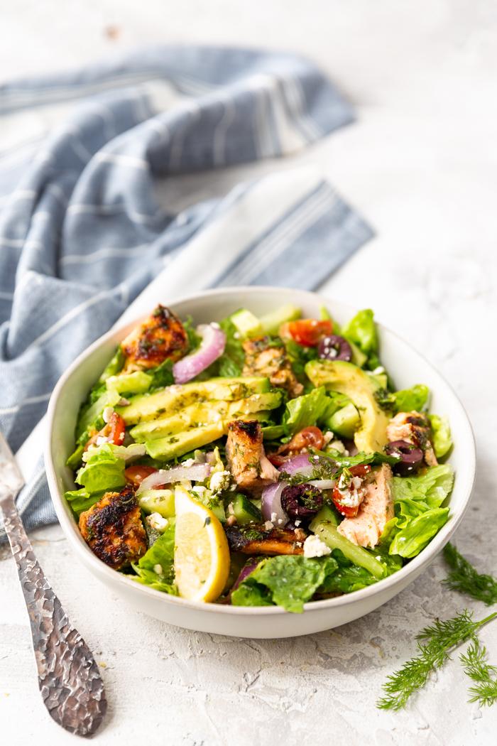 A white bowl full of salmon avocado salad