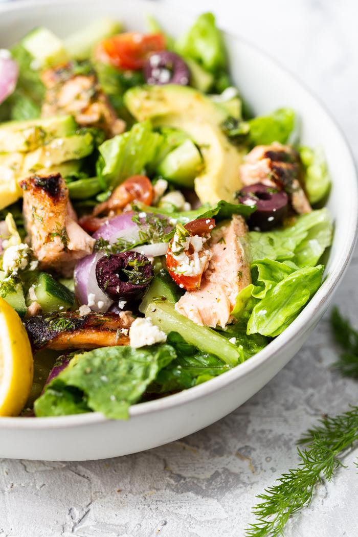 A bowl full of salmon avocado salad