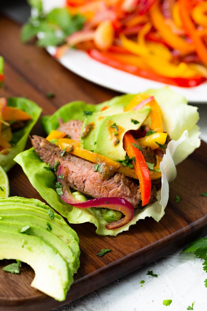 steak fajita lettuce wraps on a brown cutting board