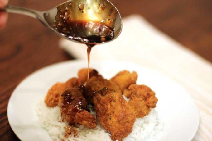 Honey Garlic Chicken spooning sauce over chicken