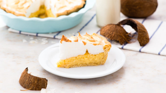 slice of coconut creme pie on a white plate with coconut shells in the foreground and back ground