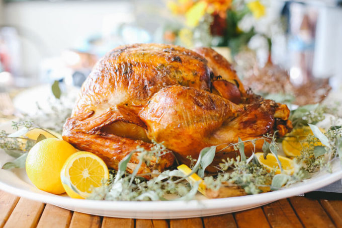 Perfectly golden turkey with tender and juicy meat on a white plate surrounded by lemons and greens