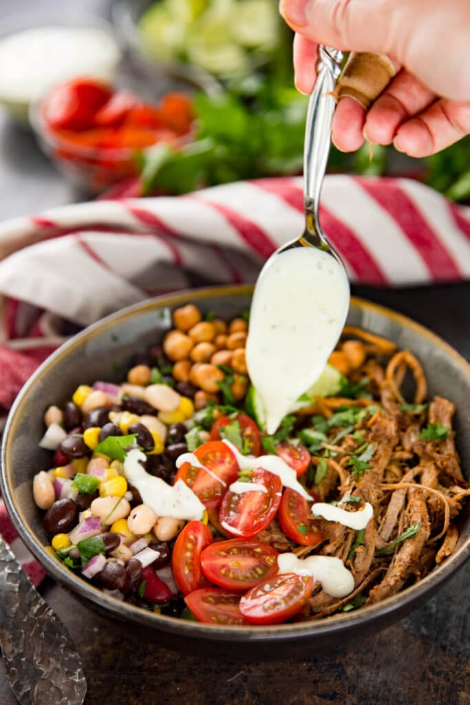 Adding dressing to a protein bowl made with pork and pulse