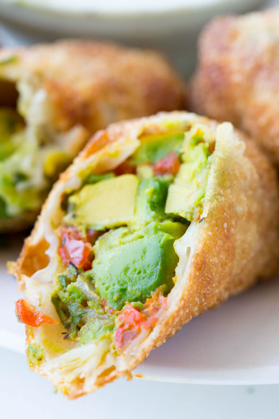 Avocado Egg Rolls: Crunchy egg roll wrapper filled with chunks of California Avocados, cilantro, tomatoes, red onion, and roasted red peppers; dipped ina creamy avocado ranch dipping sauce!
