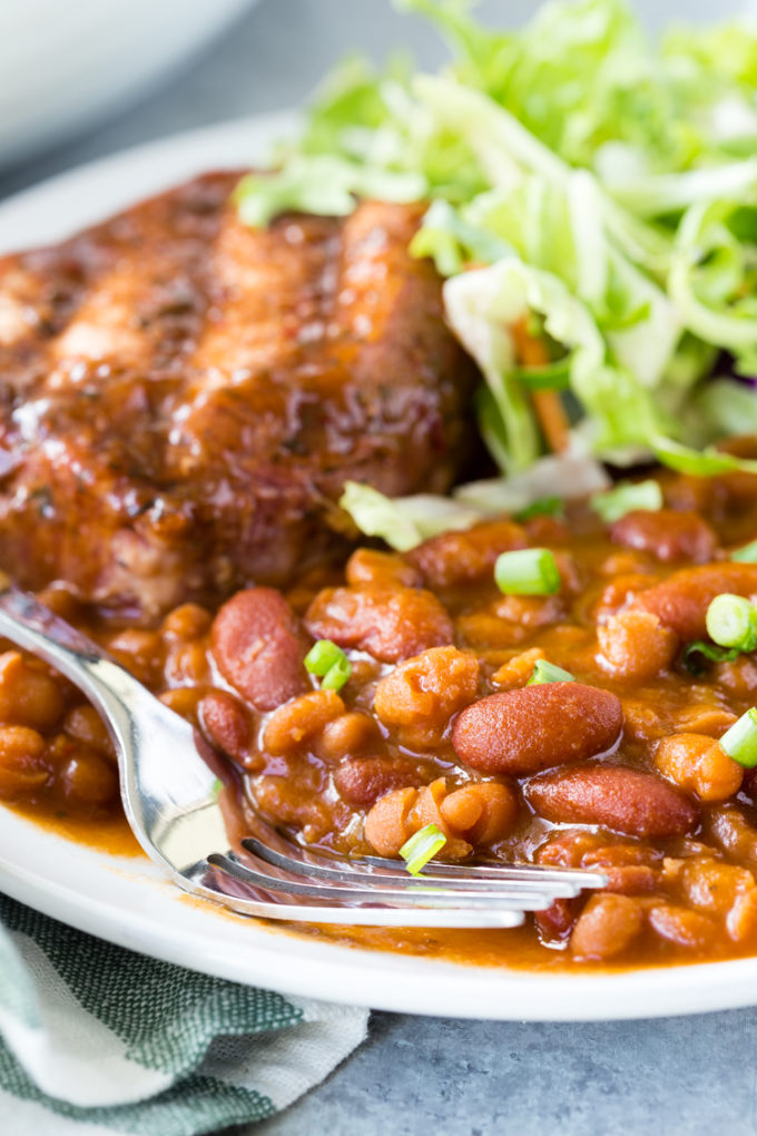Delicious and easy to make Baked beans, a white plate with baked beans, a pork chop, and greek salad, fork on the left side.