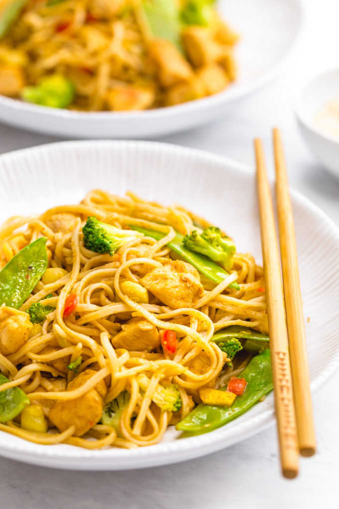 Easy garlic chicken lo mein in a white dish with chopsticks