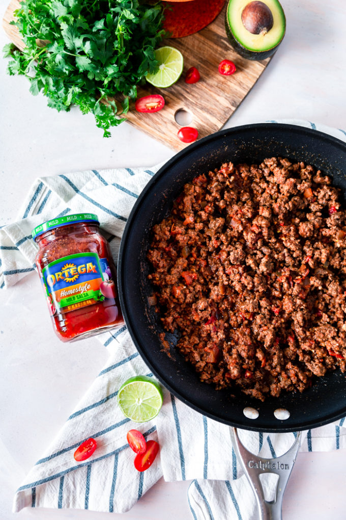 Easy Ground Beef Tacos, a skillet of ground beef taco meat, and a cutting board with taco fixings.