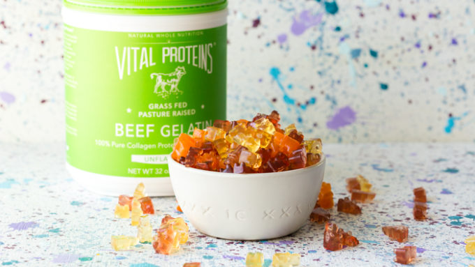 A bowl full of protein gummy bears and a bottle of collagen protein beef gelatin