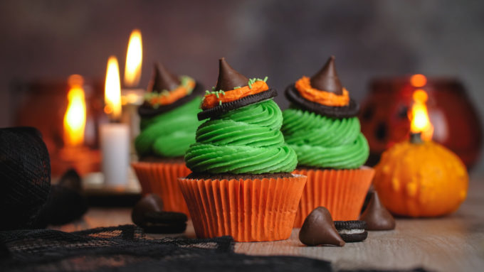 3 witch hat cupcakes with candles and a pumpkin in the background