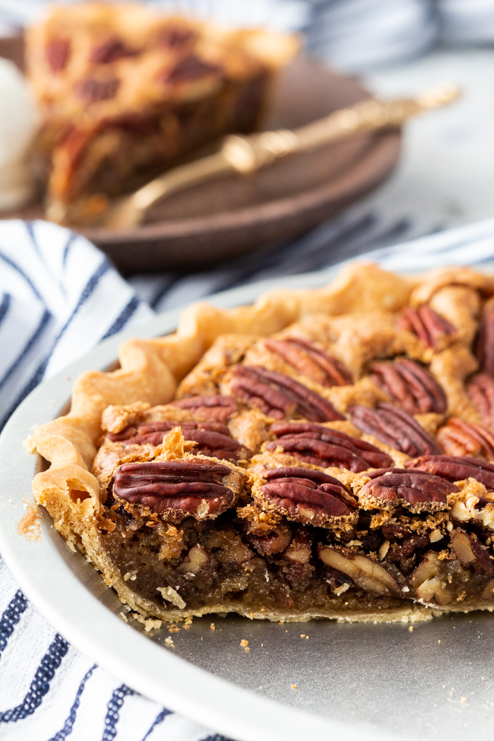 A side look at the pecan pie with a buttery, sugary filling. Crunchy pecans on top.