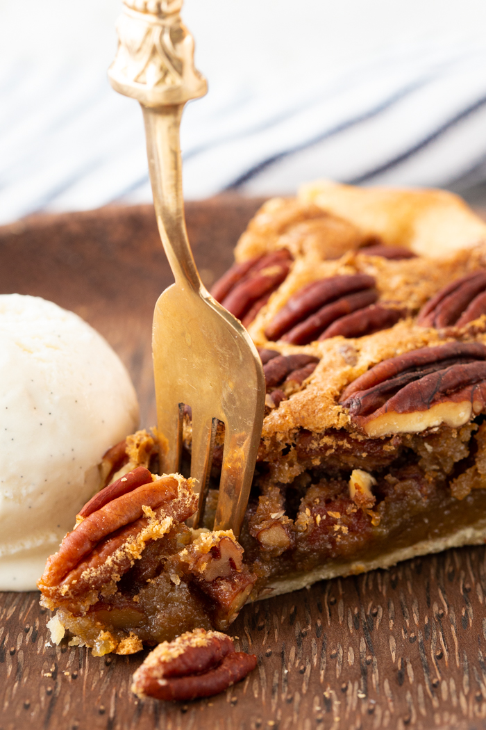A slice of pecan pie with a fork cutting off the edge.
