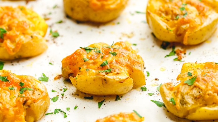 A tray of smashed Yukon gold potatoes with fresh herbs