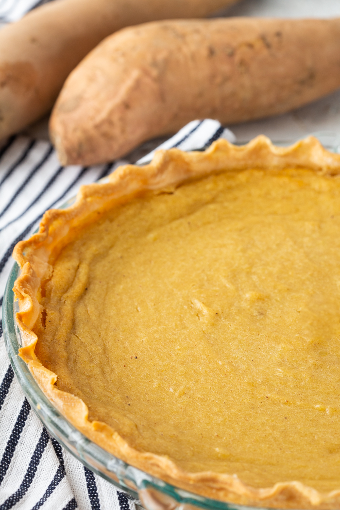 How to make a sweet potato pie. whole pie with sweet potatoes in background