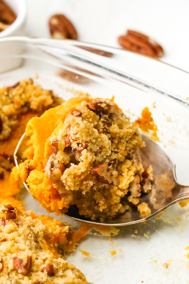 Sweet potato casserole in a spoon with a brown sugar pecan crumble topping
