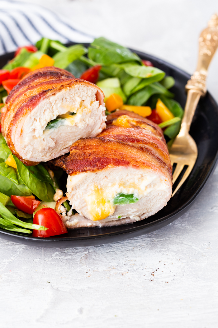 A plate of jalapeno popper stuffed chicken and spinach salad