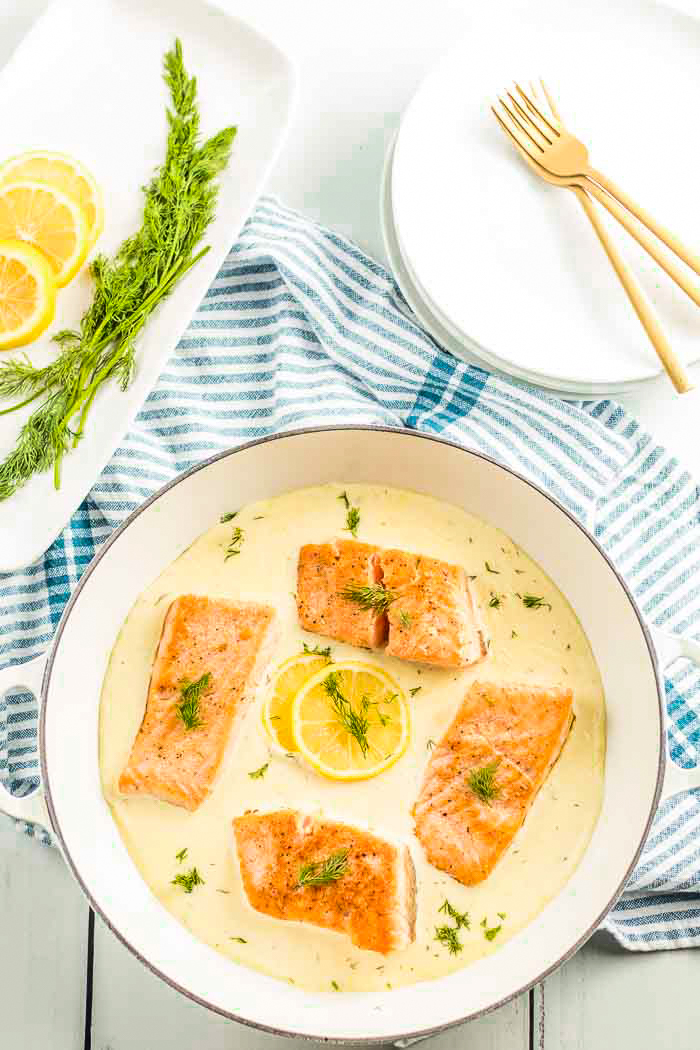 A pan full of salmon swimming in a luscious creamy lemon dill sauce