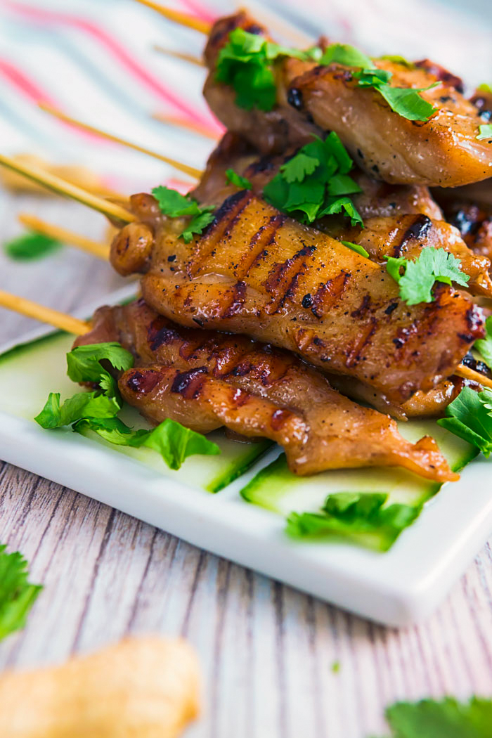 A white platter loaded with chicken satay skewers garnished with fresh cilantro.